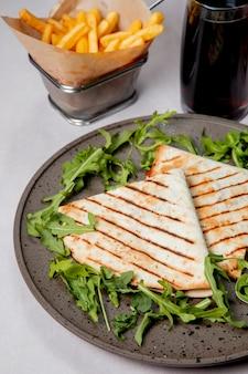 Sanduíche no lavash servido com rúcula batatas fritas