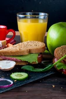 Sanduíche, ovo, xícara de café e copo de suco no café da manhã