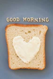 Sanduíche para o café da manhã em forma de coração com queijo em uma placa azul inscrição bom dia