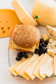 Sanduíche perto de conjunto de queijo e azeitona na placa