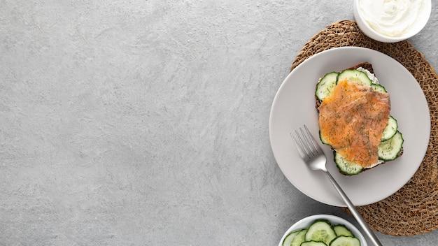 Sanduíche plano com pepinos e salmão no prato com espaço de cópia