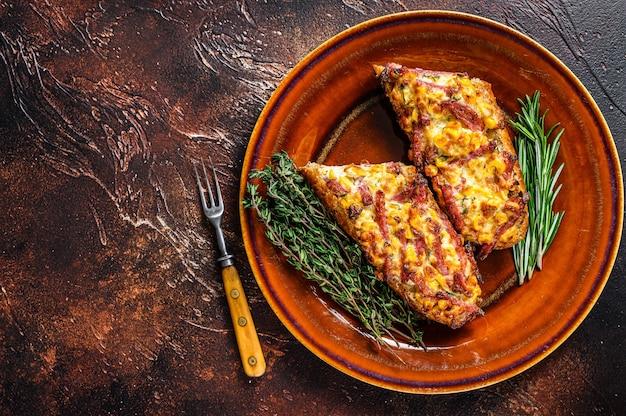 Sanduíche quente no pão baguete com presunto, bacon, legumes e queijo em um prato rústico. fundo escuro. vista do topo. copie o espaço.