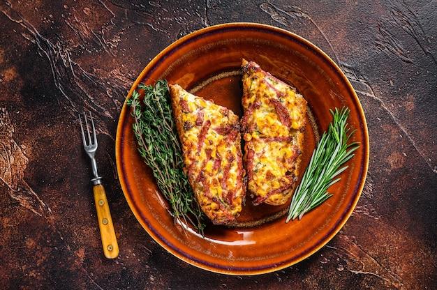 Sanduíche quente no pão baguete com presunto, bacon, legumes e queijo em um prato rústico. fundo escuro. vista do topo.