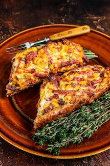 Sanduíche quente no pão baguete com presunto, bacon, vegetais e queijo em prato rústico