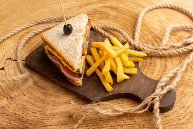 Sanduíche saboroso de frente com presunto verde-oliva, tomates e vegetais com batatas fritas em madeira