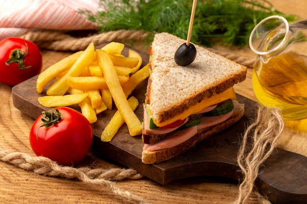 Sanduíche saboroso de vista frontal frontal com azeitona, presunto e tomate junto com batatas fritas