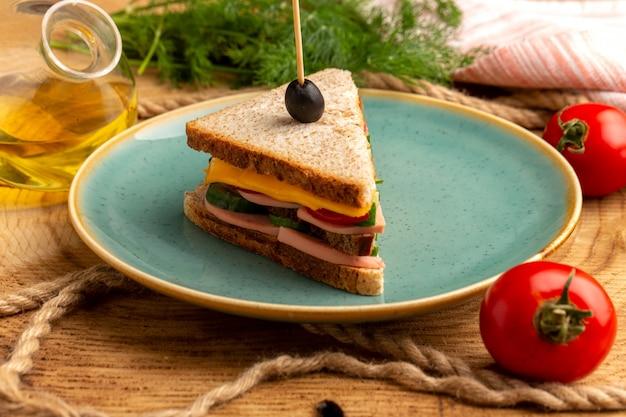 Sanduíche saboroso de vista frontal frontal com azeitona, presunto e tomate no interior da placa, juntamente com cordas