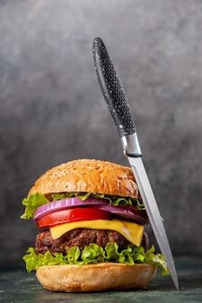 Sanduíche saboroso e faca na superfície de cor escura mista com espaço livre