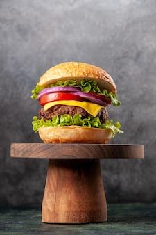 Sanduíche saboroso em uma placa de madeira em uma superfície de cor escura com espaço livre
