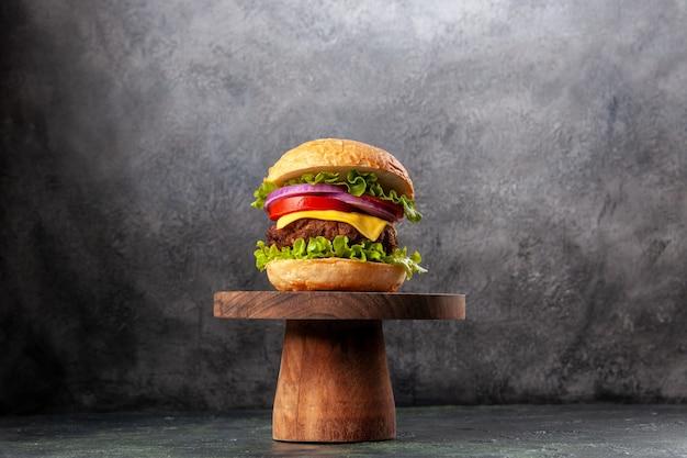 Sanduíche saboroso em uma tábua de madeira em uma superfície de cor escura