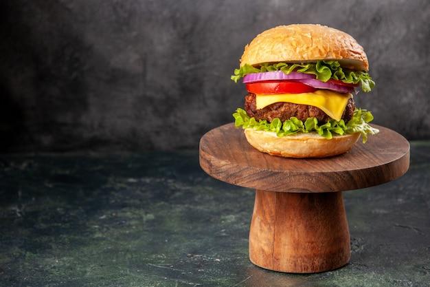 Sanduíche saboroso em uma tábua de madeira no lado esquerdo em uma superfície de cor escura mista com espaço livre