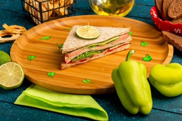 Sanduíche saboroso junto com óleo de pimentão verde e limão no azul