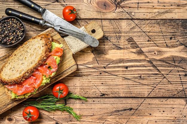 Sanduíche saudável com abacate e salmão. fundo de madeira. vista do topo. copie o espaço.