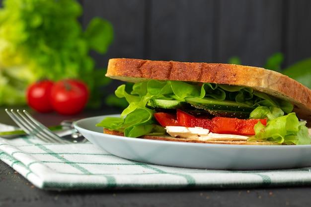 Sanduíche saudável com legumes no escuro de madeira