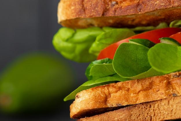 Sanduíche saudável com legumes no fundo escuro de madeira
