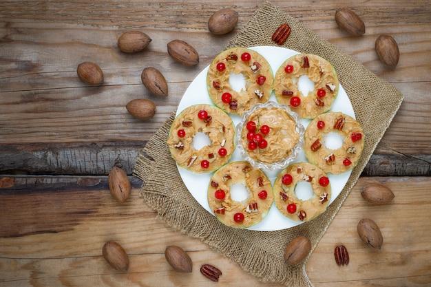 Sanduíche saudável. rodadas de maçã verde com manteiga de amendoim e groselha e nozes pecã na vista superior, rústica
