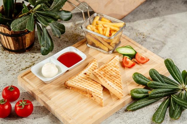 Sanduíche servido com batatas fritas e molho sobre uma tábua