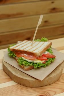 Sanduíche suculento com bacon, legumes frescos, salada verde e linhas escuras depois de grelhar na placa de madeira