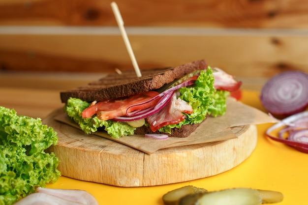 Sanduíche suculento com pão escuro e bacon grelhado espera por você na placa de madeira