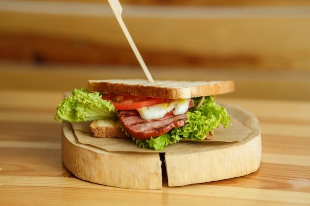 Sanduíche suculento com pão grelhado e bacon espera por você na placa de madeira