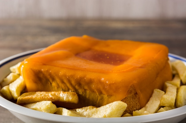 Sanduíche típico de francesinha portuguesa com batatas fritas na mesa de madeira