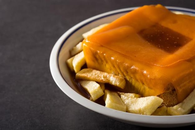 Sanduíche típico de francesinha portuguesa com batatas fritas no preto