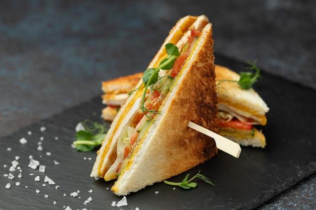 Sanduíche torrado com filé de frango, queijo, salada, pepino e tomate em uma placa de ardósia preta