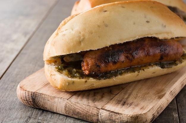 Sanduíche tradicional de choripan argentina com molho de chouriço e chimichurri na mesa de madeira