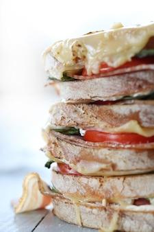 Sanduíche vegan grande com legumes e queijo na mesa de tábua de madeira
