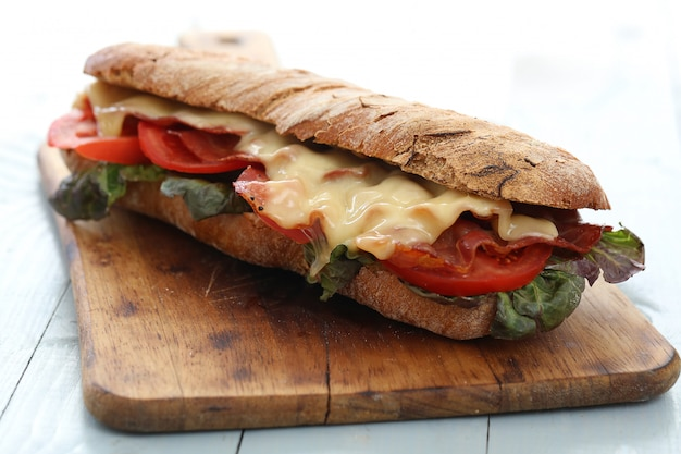 Sanduíche vegan grande com legumes na mesa da mesa de madeira