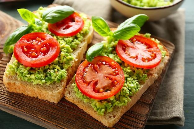 Sanduíche vegano com abacate e vegetais na tábua, em superfície de madeira