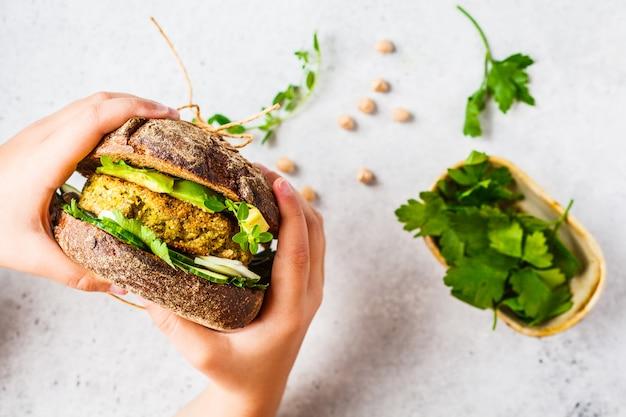 Sanduíche vegano com patty de grão de bico, abacate, pepino e verduras no pão de centeio