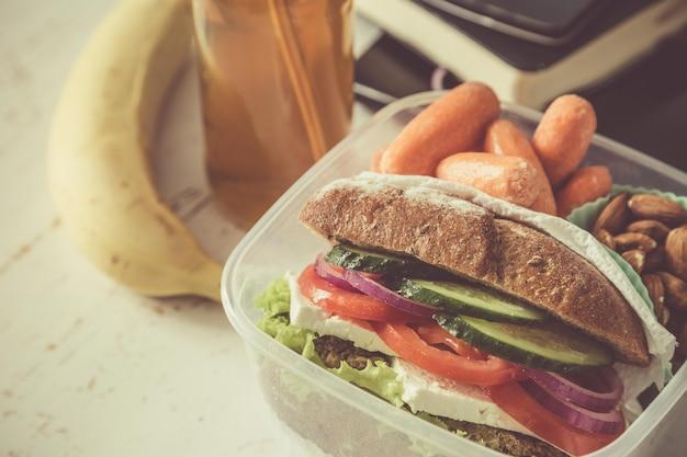Sanduíche vegano na lancheira com cenouras e nozes
