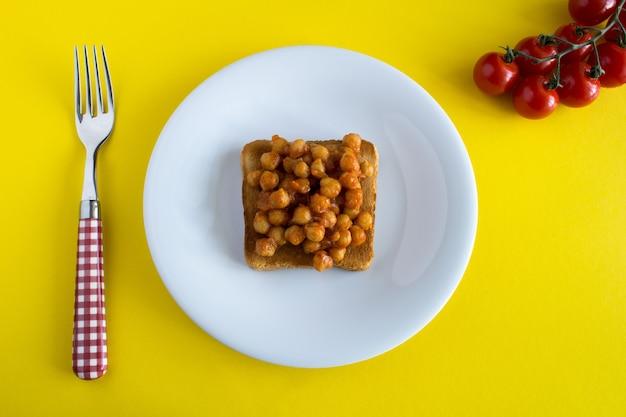 Sanduíche vegetariano com grão de bico em molho de tomate na chapa branca na superfície amarela. vista superior.