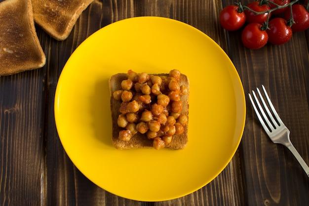 Sanduíche vegetariano com grão de bico em molho de tomate na placa amarela. vista superior.