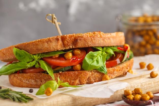 Sanduíche vegetariano com tomate, pepino, grão de bico frito e manjericão na placa de madeira. conceito de comida vegetariana saudável.