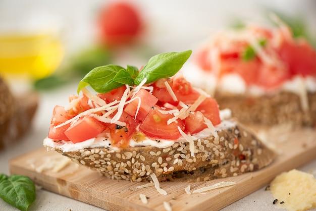 Sanduíche vegetariano com tomate rosa, parmesão e manjericão