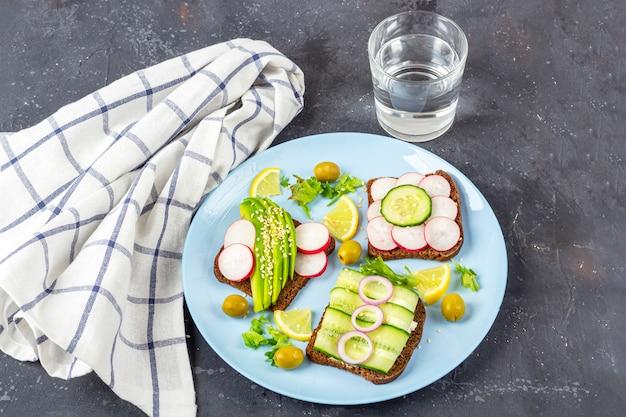 Sanduíche vegetariano de superalimento aberto com diferentes coberturas: abacate, pepino, rabanete no prato com um copo de água no fundo escuro. alimentação saudável. alimentos orgânicos e vegetarianos. feche acima, copie o espaço