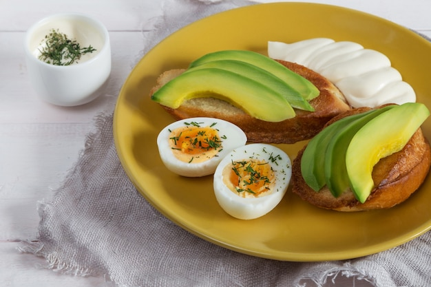 Sanduíches abertos com abacate, ovos e molho