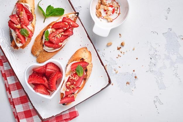 Sanduíches abertos com morangos, queijo de menta e noz em uma placa de cerâmica sobre um fundo de pedra cinza claro. verão e dieta alimentar saudável, conceito de comida vegetariana. vista do topo.