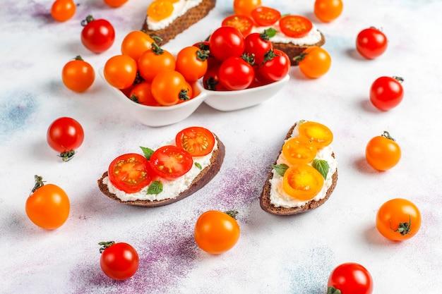 Sanduíches abertos com queijo cottage, tomate cereja e manjericão.