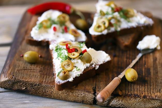 Sanduíches abertos com queijo mascarpone, azeitonas e ervas. comida saudável. snack keto.