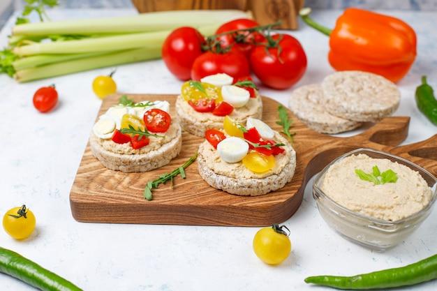 Sanduíches abertos de bolos de arroz com homus, legumes e ovo de codorna, café da manhã ou almoço saudável