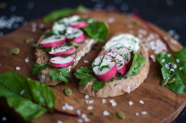 Sanduíches abertos no pão de centeio escuro com ovos, camarões, rabanetes, pepino e creme de queijo