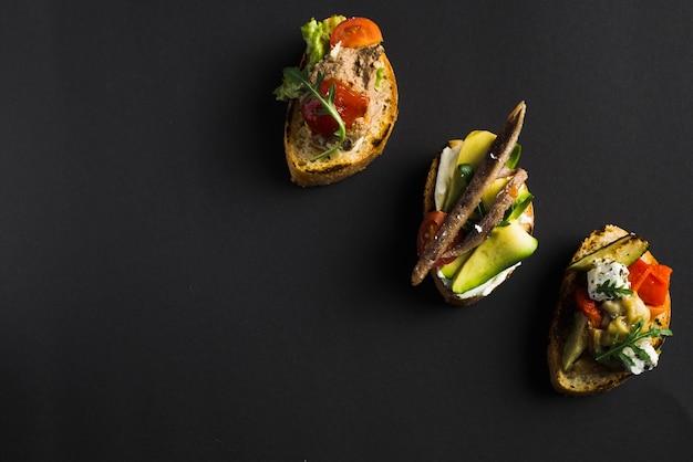 Sanduíches abertos palatáveis em preto