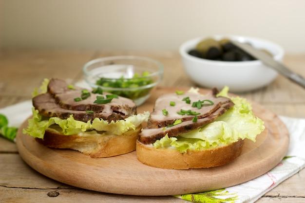 Sanduíches apetitosos com carne, alface e molho servidos com azeitonas. estilo rústico.