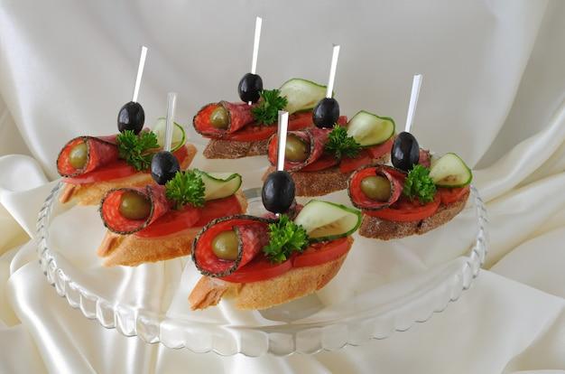 Sanduíches canapés de salame com azeitonas em um prato
