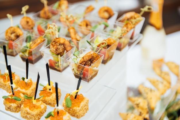 Sanduíches, canapés e bolos na mesa festiva. grande variedade de petiscos