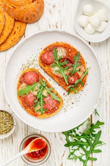 Sanduíches caseiros abertos com linguiça, queijo mussarela e rúcula fresca