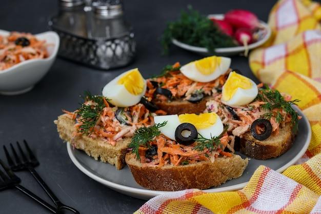 Sanduíches caseiros com cenouras e rabanetes, decorados com ovo cozido e azeitonas pretas em um prato contra um escuro